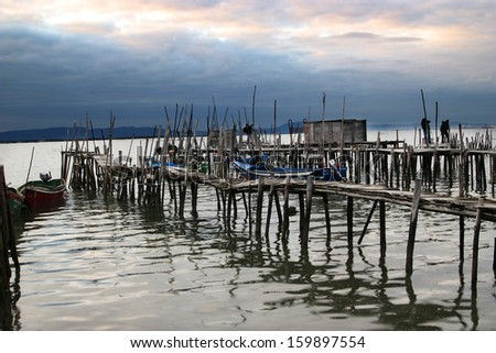rustic quay with boats at the end of the day - stock photo