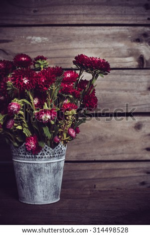 Rustic red flowers in a can vase on an old vintage wooden board background