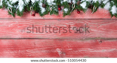 Rustic red wooden background for Christmas concept with snowy fir branches, candy canes, red berries and pine cones. Overhead view with copy space.