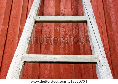 Rustic red wooden ladder reaching upwards - stock photo