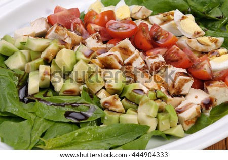 rustic salad with spinach, avocado, diced chicken, tomatoes and eggs