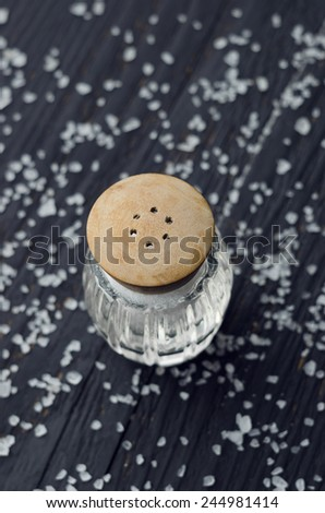 Rustic salt shaker over black wooden table with salt all over it - stock photo