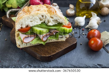 Rustic sandwich with ham, ciabatta bread,fresh salad,tomatoes and cucumber on wooden cutting board - stock photo