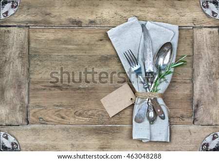 Rustic set of cutlery knife, spoon, fork with Rosemary, wooden background. Top view