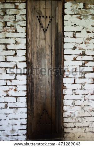Rustic smokehouse door on white brick wall