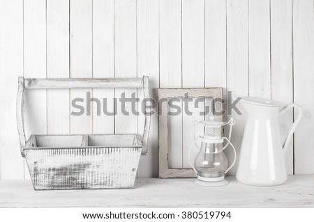 Rustic still life in white color: shabby wood box and photo frame, jug and lantern against white wood wall.