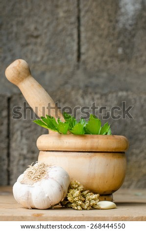 Rustic still life of aromatic herbs with a wooden mortar