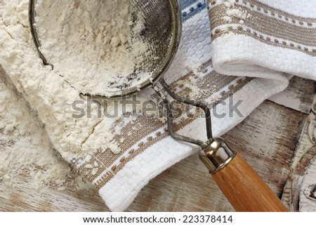 Rustic still life of baking flour with vintage sieve and kitchen towel on distressed wood.   - stock photo