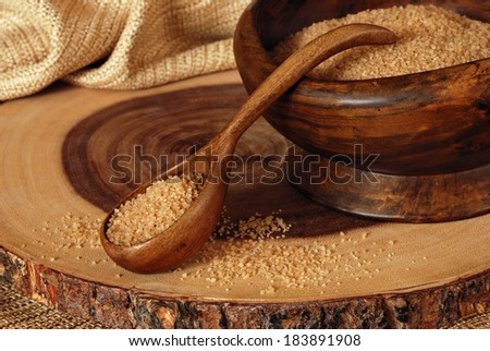 Rustic still life of vintage, handcrafted wooden bowl and spoon filled with pure cane sugar sitting on a natural acacia wooden serving tray.  Closeup with shallow dof. - stock photo