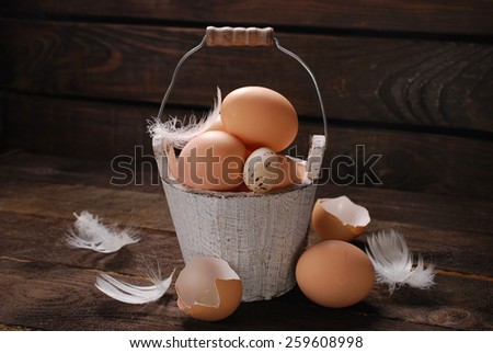 rustic still life with eggs in vintage wooden bucket on plank background for easter - stock photo
