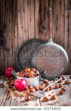 Rustic still-life with raw edible chestnuts in a pan, apples and vintage kitchen utensils on old wooden background - stock photo