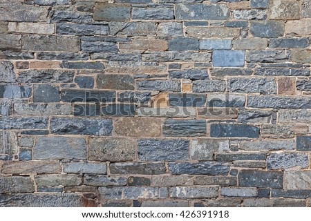 Rustic stone wall background with blue and gray tones - stock photo