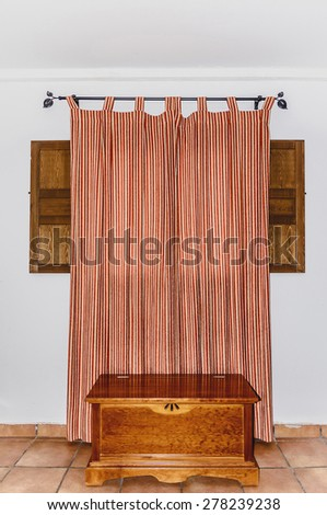 Rustic style decoration in a room. Closed curtain on a wooden window. Typical rural style in spain - stock photo