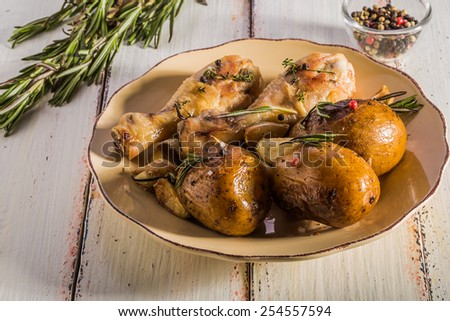 Rustic style potatoes and chicken with rosemary, garlic on a wooden white background - stock photo