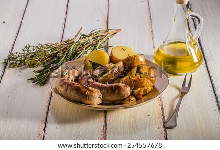 Rustic style potatoes and fried sausages with rosemary, garlic on a wooden white background - stock photo