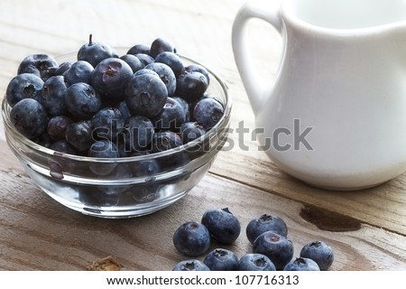 Rustic table setting of blueberries and a small white milk pitcher