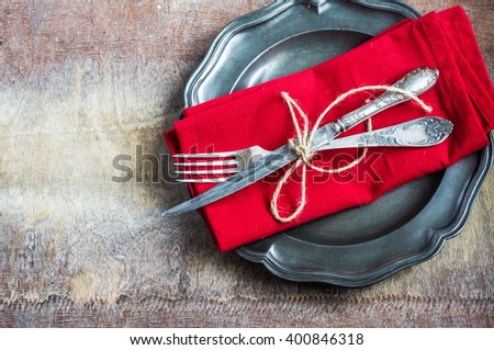 Rustic table setting with bright napkin, silverware and plate on old wooden table. View from above with copy space - stock photo