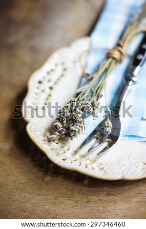 Rustic Table Setting with napkin, silverware and dry lavendre lowers on old wooden table - stock photo