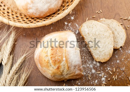 Rustic table with fresh bread, grains and ears of wheat. Top view.