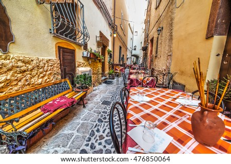 rustic tables and chairs by a trattoria in Sardinia, Italy