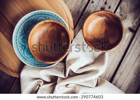 Rustic tableware, wooden bowls and ceramic plates with a linen cloth on an old vintage board.