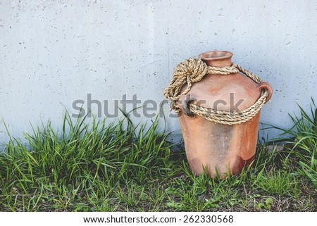 Rustic terracotta clay pot on concrete and grassy background (Shallow DOF) - stock photo