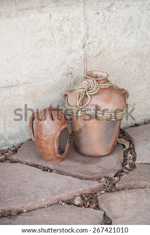 Rustic terracotta clay pots on slate and concrete background (Shallow DOF) - stock photo