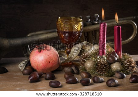 Rustic traditional christmas still-life with wine, seasonal fruits and a old trumpet - stock photo