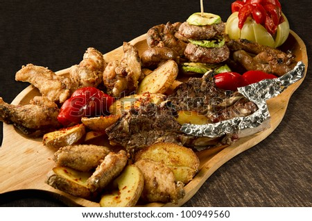 Rustic tray with various meats, cheese balls and assorted vegetables - isolated - stock photo