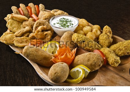 Rustic tray with various meats, cheese balls and garlic sauce - isolated - stock photo