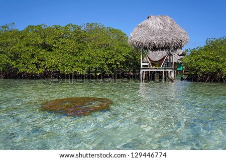 Rustic tropical hut with hammock and thatched roof over the sea between islets of mangrove, Caribbean, Central America - stock photo