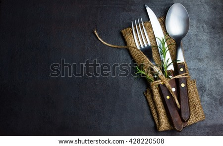 Rustic vintage set of cutlery knife, spoon, fork. Black background. Top view - stock photo
