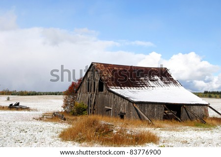 Rustic, weathered barn needs help from boards to continue to stand.  Roof has snow as well as surrounding field. - stock photo