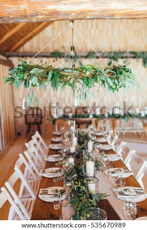 Rustic wedding decor wedding wreath chandelier stock photo edit now rustic wedding decor wedding wreath chandelier decorated with eucalyptus and decorated wedding table aloadofball Choice Image