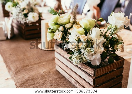 rustic wedding decorations. wooden box with bouquet of flowers on table with bagging cloth