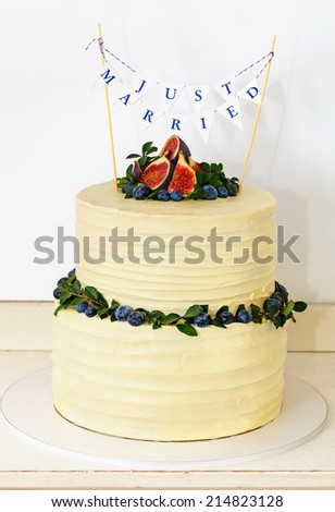 Rustic white wedding cake topped with fig and berries - stock photo
