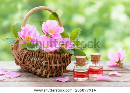 Rustic wicker basket with pink rose hip flowers and bottles of essential roses oil. - stock photo