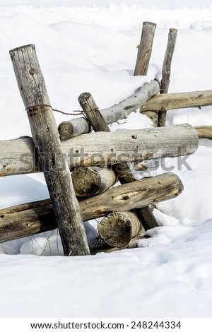 Rustic wilderness fence post in the snow - stock photo