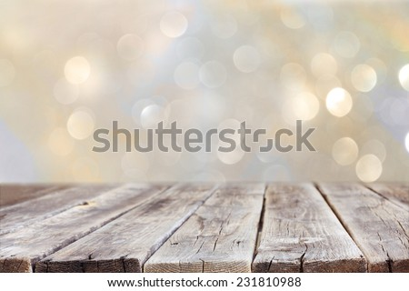 rustic wood table in front of glitter silver and gold bright bokeh lights  - stock photo