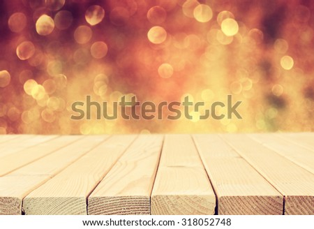 rustic wood table in front of glitter silver and gold bright bokeh lights. filtered image  - stock photo
