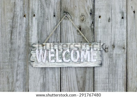 Rustic wood welcome sign hanging on old weathered wooden fence - stock photo