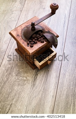 Rustic wooden antique manual coffee grinder with open drawer and handle on wood surface. - stock photo