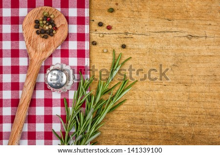 Rustic wooden background with checkered tablecloth and wooden spoon - stock photo
