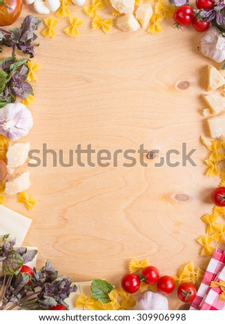 Rustic wooden background with italian food ingredients. Pasta, tomatoes, parmesan, mozzarella, basil, garlic - stock photo