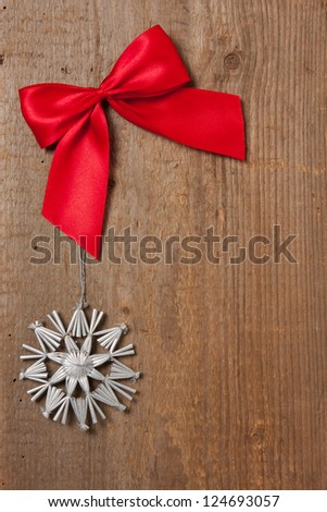 Rustic wooden board with red ribbon and silver star