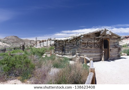 Rustic wooden cabin in Arizona desert with bushes in the foreground and a rail fence - stock photo