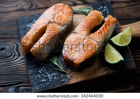 Rustic wooden chopping board with pan fried trout steaks, studio shot - stock photo
