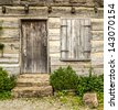 Rustic wooden door and shutters on a very old house - stock photo