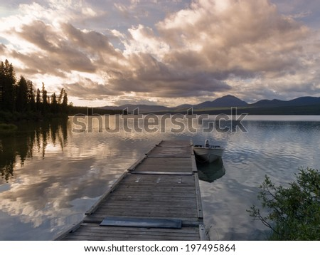 Rustic wooden floating dock or jetty on a tranquil lake, small john boat moored and dramatic clouds sunset reflected on still water - stock photo