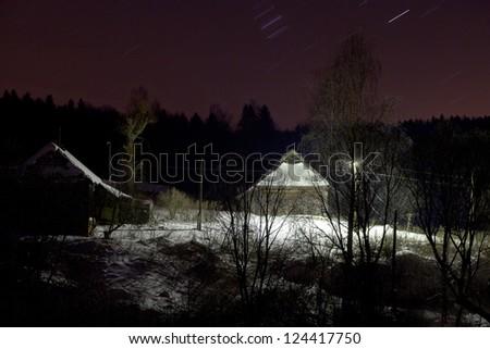 rustic wooden house under snow at dark winter night - stock photo
